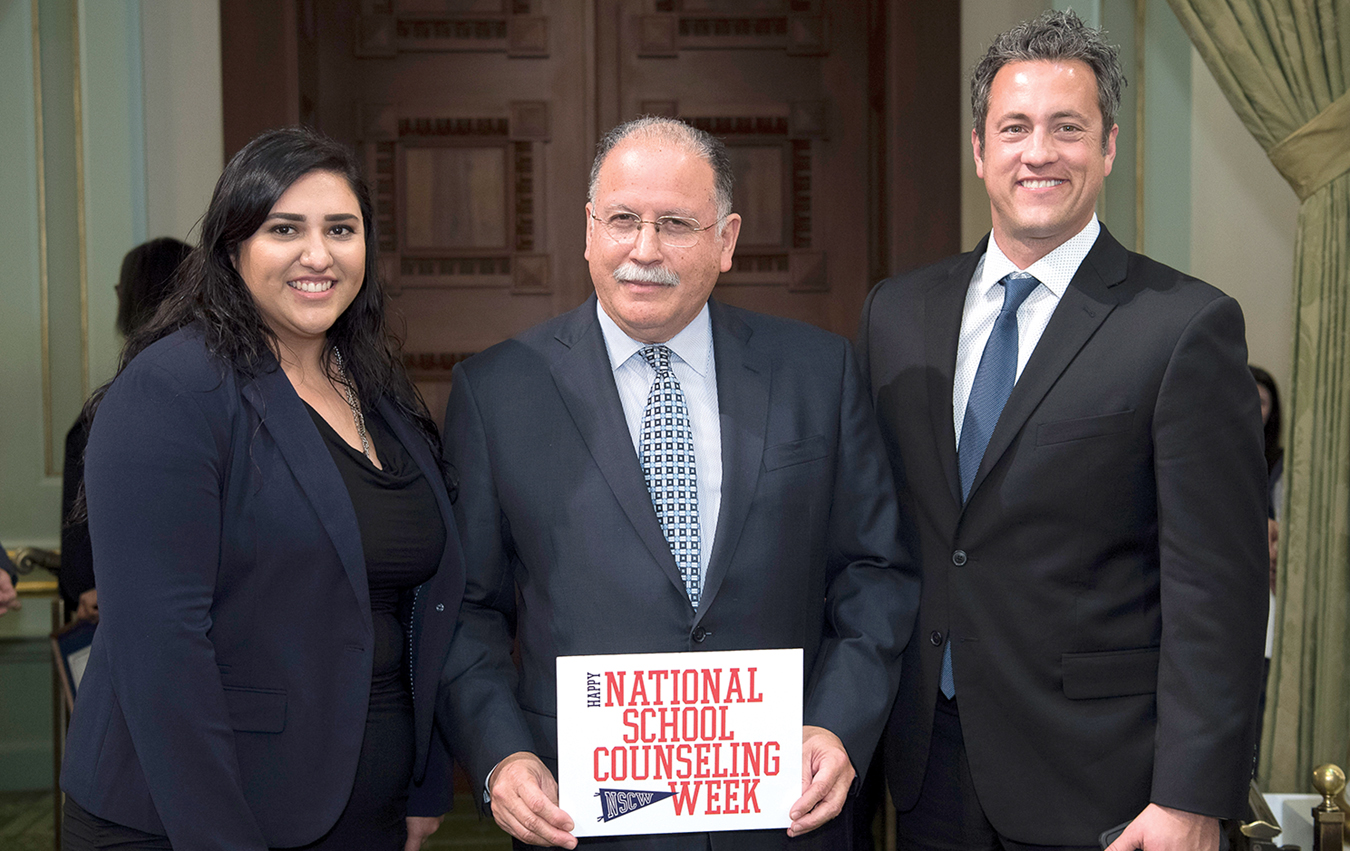 L-R, School Counselor Yuri Nava, Assembly member Jose Medina, and Principal Michael Roe pose on the floor of the State Assembly recently when Nava was honored for her work.